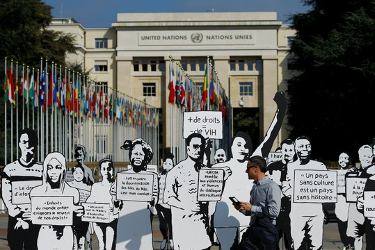"""People walk past around a hundred silhouettes and slogans installed on the Place des Nations for a project called """"Les Grandes Marches"""" (The Big Steps) at the United Nations in Geneva"""