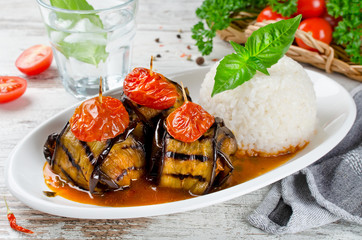 Meatballs wrapped in eggplant on a plate of rice