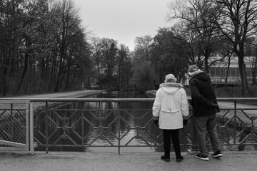 Two old persons grandmother and grandfather standing and looking at the water. Black and white.