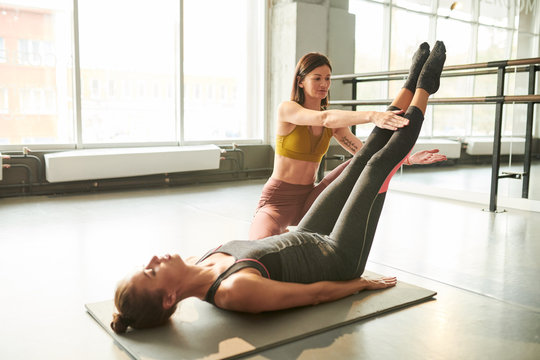 Full length portrait of contemporary young woman doing stretching exercises during fitness workout in health club with female instructor helping her, copy space