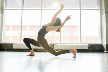 Full length portrait of contemporary young woman dancing passionately in studio lit by serene sunlight, copy space