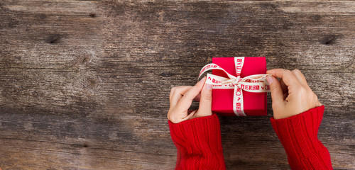 Christmas gift giving - someones hand in red knitted sweater making bow on red box with present, banner