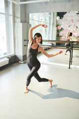 Full length portrait of contemporary young woman dancing in sunlight indoors, copy space