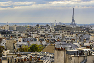The roofs of Paris and its chimneys under a clouds sky