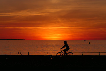 Romantic sunset with a cyclist - A cyclist rides a path in front of the sea. In the background the sun sets in the ocean. The person is only seen as a silhouette. Everything is orange.