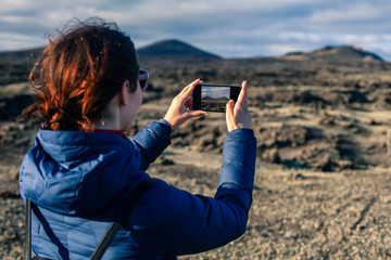 Young traveler woman taking photo of scenic volcanic landscapes in Lanzarote