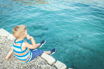 Little boy throwing stones in the water while sitting on a pier.