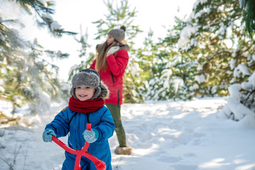 Happy little boy and his mother go for a walk in winter park