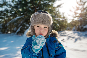 Happy cute little boy dressed in warm coverall and hat in winter frozen snowy forest