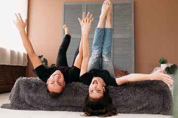 Boy and girl raise their legs up lying on a bed in a cosy room