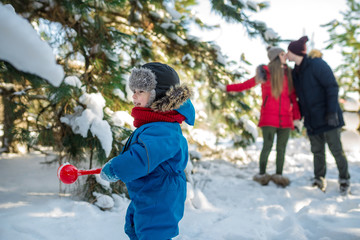 Little boy play with snow and his parents kiss