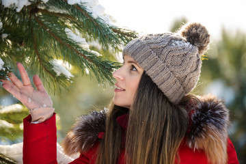 Attractive young woman in hat keeps snowy spruce branch in winter park