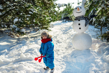 Little boy plays in snow and makes snowballs