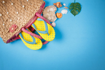 Yellow sandals with woven handbags on blue color background, Summer holidays accessories . flat lay photo