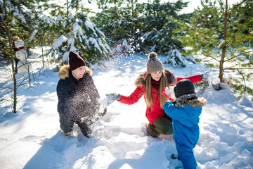 Father, mother and son play in snow in needles wood. Happy wintertima
