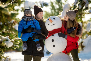 Happy family with snowman in winter park
