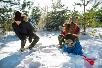 Father, mother and son play snowballs in winter park