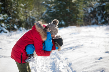 Happy young mother and her son have fun in winter