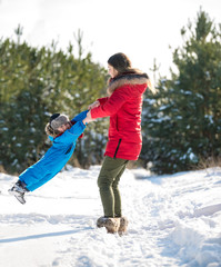 Happy young mother and her son have fun in winter. Play in snow