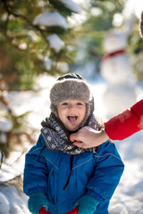 Happy cute little boy dressed in warm coverall and hat in winter frozen snowy forest. Mother care