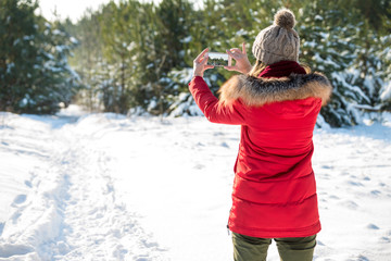 a girl stands back and makes photo on smartphone in winter forest