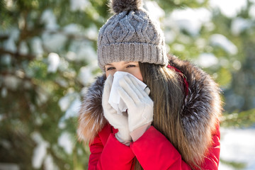 A girl in hat and warm coat blows her nose in paper handkerchief in winter outdoor