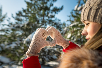Female Hands Making Finger Shape Of A Heart Sign in winter snowy forest