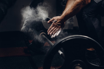 Weightlifter preparing for training workout lifter barbell. Hands in dust and talc. Dark background.