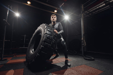 Muscular fitness man flipping tire wheel. Concept lifting, workout training.