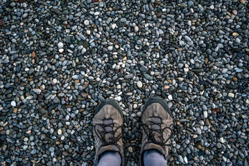 feet in sneakers on a pebble beach