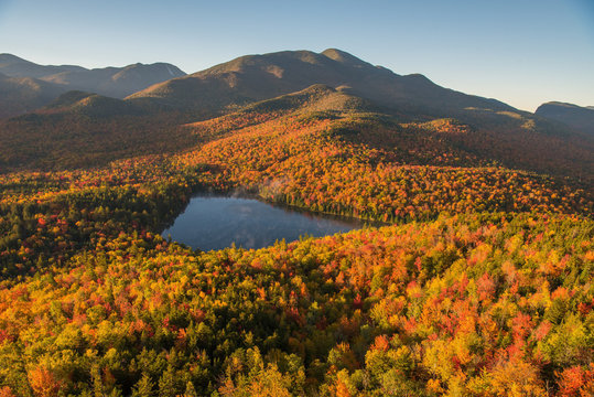 Morning light illuminates the fall color in the Adirondack Mountains over Heart Lake