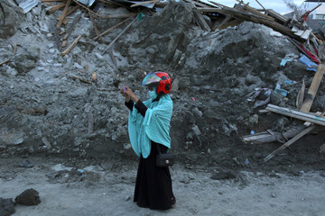 A woman takes pictures while visiting Petobo neighbourhood which was hit by an earthquake and liquefaction in Palu
