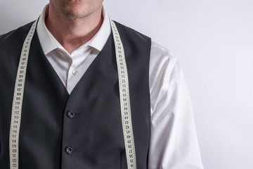Well dressed tailor in white shirt and black suit vest have measuring tape hanging around neck. White background with copy space for text.