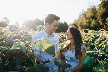 Cheerful man and pregnant woman hug each other tender standing in the field with tall sunflowers around them