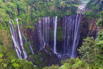 Majestic view of Tumpak Sewu Waterfall or also known as Coban Sewu, is a waterfall with 120 metres high, located in Sidomulyo Village, Pronojiwo District, Lumajang Regency, East Java, Indonesia.
