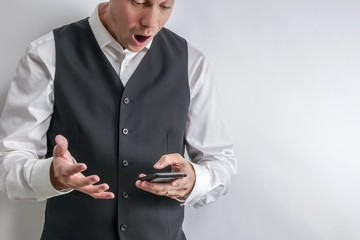 Well dressed man in white shirt and black suit vest loooking at his smart phone. Looks shocked, surprised and happy. White background with copy space for text.