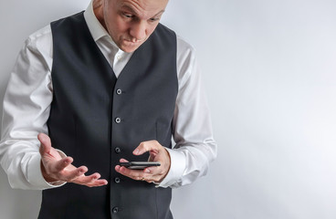 Well dressed man in white shirt and black suit vest loooking at his smart phone. Looks frustrated, irritated and angry. White background with copy space for text.
