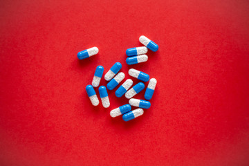 Bunch of blue and white medication pills on a solid red background