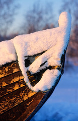Bow of an old rowboat covered with snow.