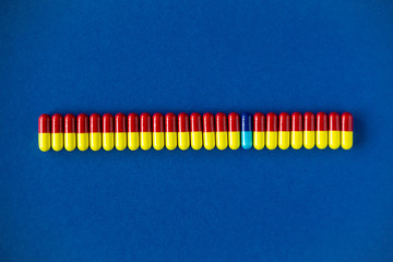 Line of colourful and contrasted medication pills on a solid blue background