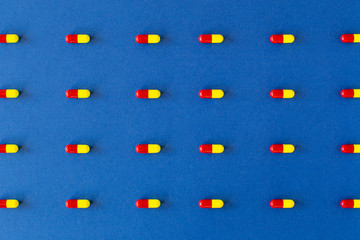 Linear colourful pill composition on a solid blue background