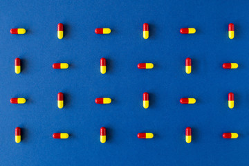 Colourful pill crossed composition on a solid blue background