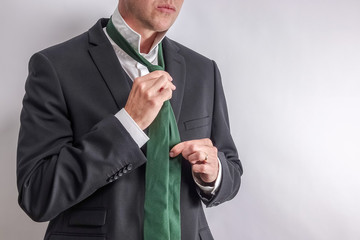 Well dressed man in white shirt and black suit get dressed / undressed. Shirt collar unfold and corrects his tie. White background with copy space for text.