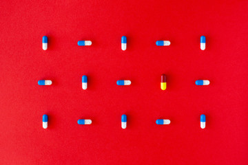 Graphic colourful pill composition on a solid red background