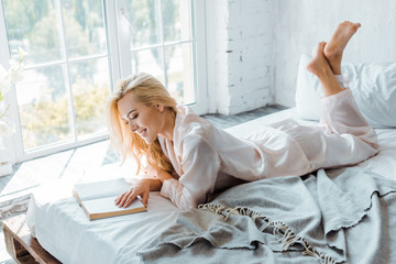 beautiful smiling girl in pajamas lying on bed and reading book