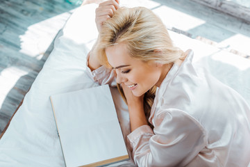 overhead view of beautiful happy girl lying on bed and reading book