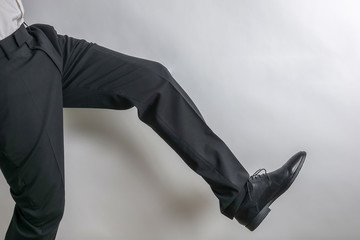 Legs and shoes from a well dressed businessman in a black suit. White background with copy space for text.