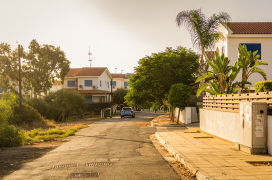 Countryside street with cottages, homes, palm trees and car at sunset