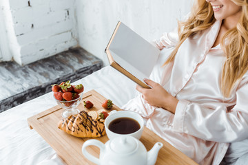 cropped image of attractive woman in pajamas reading book, breakfast on wooden tray in bed