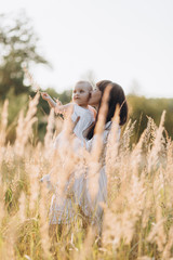Beautiful portrait of charming mother and lovely little daughter walking across the field in the rays of evening sun